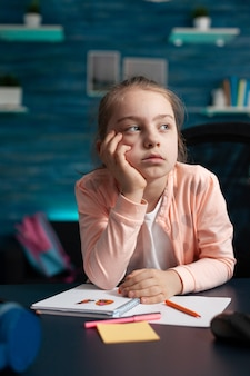 Uma criança sonhadora pensando em desenho de arte criativa enquanto trabalhava na aula de pintura da escola