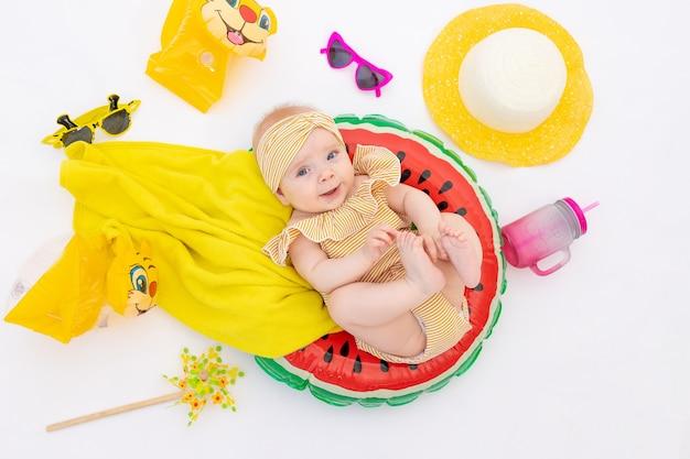Uma criança sorridente com um anel de natação em um maiô, toalha e óculos de sol encontra-se sobre um fundo branco e isolado. férias no mar com o bebê, conceito