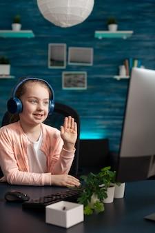 Uma criança sorridente com um fone de ouvido cumprimentando o professor remoto durante uma videochamada online