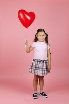 Uma criança sorridente e sorridente em um vestido rosa com um balão vermelho em forma de coração na mão