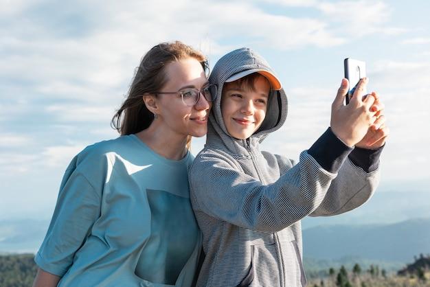 Uma criança tira uma selfie em um smartphone com a mãe em uma viagem pela montanha