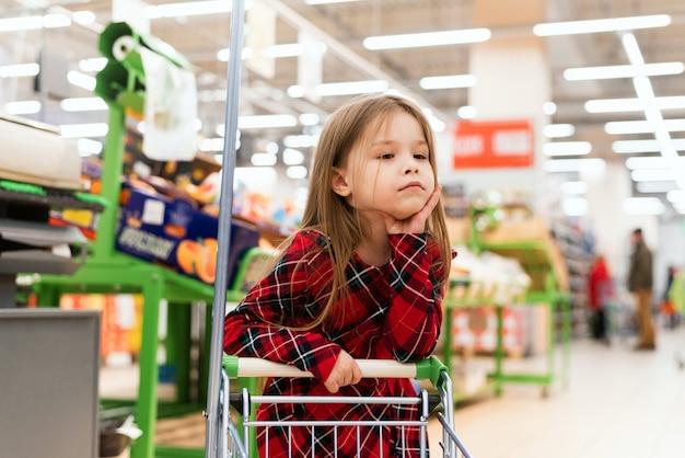 Uma criança triste fica atrás do carrinho e seleciona os produtos para casa. prateleiras vazias nas lojas, pandemia e histeria devido a coronavírus
