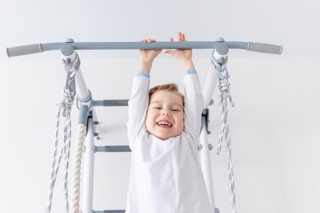 Uma criança, um menino, escala na parede sueca da casa