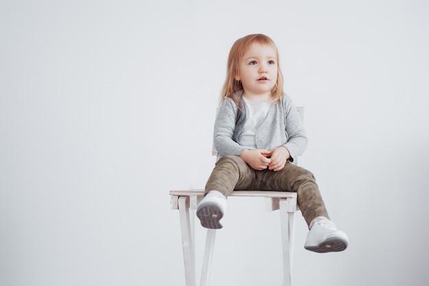 Uma criança, uma menina sentada em um banquinho alto rindo