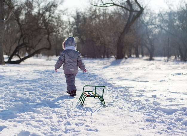 Uma criança vai e arrasta um trenó em uma clareira nevada na floresta