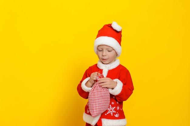 Uma criança vestida com uma fantasia vermelha de papai noel está segurando um pequeno saco com presentes de ano novo
