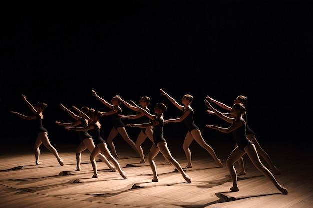 Uma dança coreografada de um grupo de graciosas jovens bailarinas praticando no palco de uma escola de balé clássico