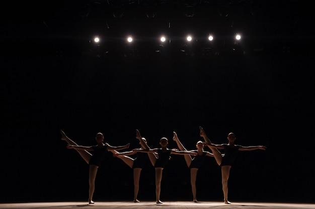 Uma dança coreografada de um grupo de graciosas jovens bailarinas praticando no palco