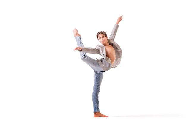 Uma dançarina de balé adolescente posa descalça, isolada em um fundo branco.