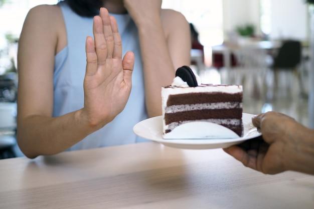 Uma das garotas de saúde usou uma mão para empurrar um prato de bolo de chocolate.
