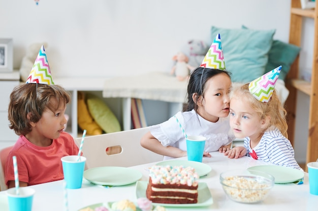 Uma das garotas fofas com bonés de aniversário sussurrando algo para a amiga enquanto está sentada à mesa festiva com um garoto próximo