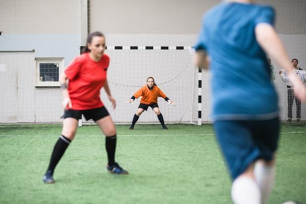 Uma das jovens mulheres ativas em roupas esportivas em pé nos portões do campo de futebol durante o treinamento, pronta para pegar a bola