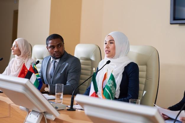 Uma das jovens oradoras em hijab falando no microfone enquanto faz um discurso na frente do público em uma conferência de negócios ou política