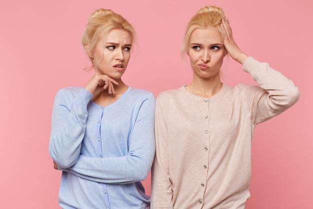 Uma das lindas gêmeas loiras esqueceu onde estão as chaves do carro, e sua irmã fica perplexa e com raiva dela. irmãs isoladas sobre fundo rosa.