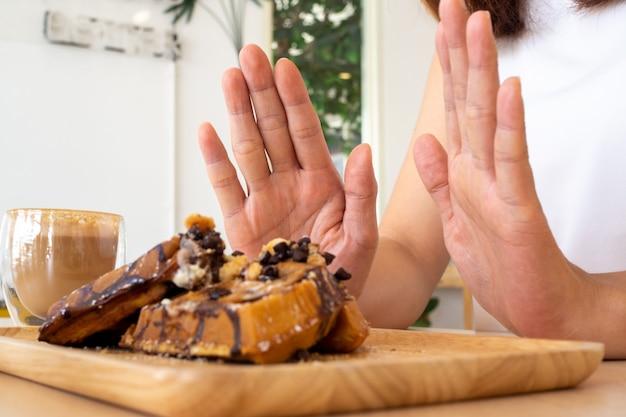 Uma das meninas da assistência médica usou a mão para empurrar um prato de bolo de chocolate. recuse-se a comer alimentos que contenham gordura trans.