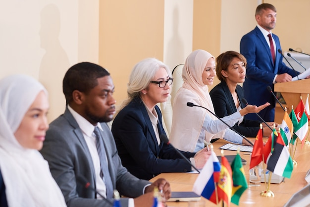 Uma das mulheres muçulmanas em um hijab tradicional explicando seu ponto de vista a um delegado estrangeiro em conferência de negócios
