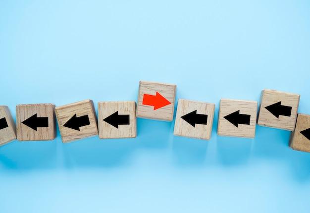 Uma das setas vermelhas move-se para a direção oposta com outras setas pretas que esculpidas em cubos de blocos de madeira para a interrupção dos negócios e o conceito de ideia de pensamento diferente.