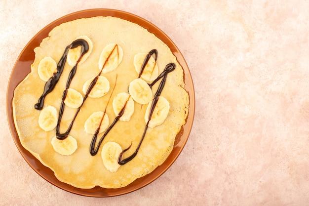 Uma deliciosa fatia de sobremesa com vista de cima desenhada com chocolate e bananas dentro de um prato redondo marrom na mesa rosa