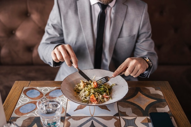 Uma deliciosa refeição no restaurante. um close-up de um prato com comida moderna comido por um homem em um terno de negócios e com um relógio no pulso. almoço, estilo de vida de negócios