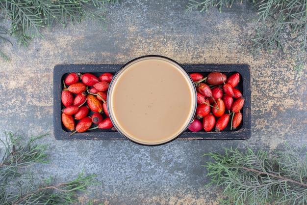 Uma deliciosa xícara de café com roseiras no tabuleiro escuro. foto de alta qualidade