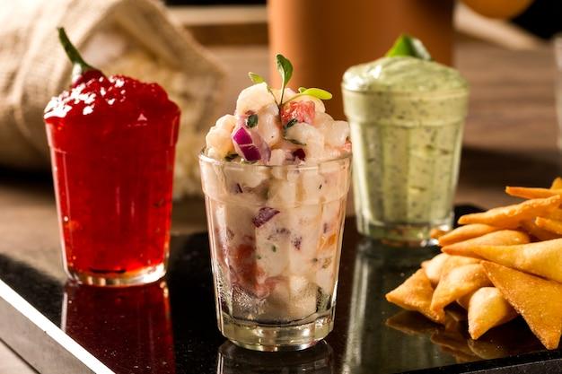 Uma deliciosa xícara de guacamole, geleia de pimenta picante, ao lado de ingredientes frescos em uma mesa com tortilla chips e salsa