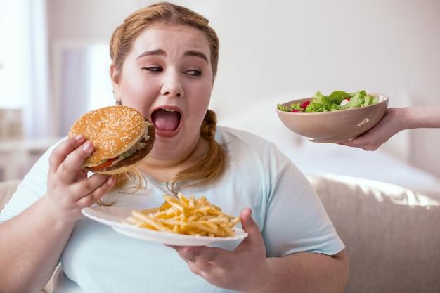 Uma dentada. mulher ruiva gordinha olhando para uma salada deliciosa enquanto come hambúrguer com batatas fritas