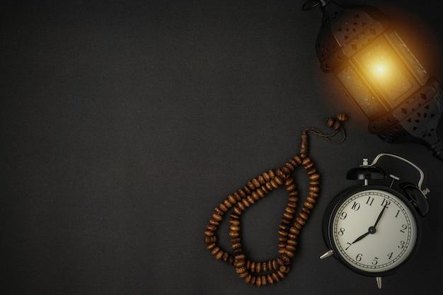 Uma deslumbrante lanterna de vela do ramadã e contas de rosário em fundo preto copie o espaço