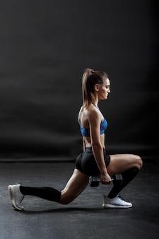 Uma desportista com penteado de rabo de cavalo está fazendo exercícios de fitness