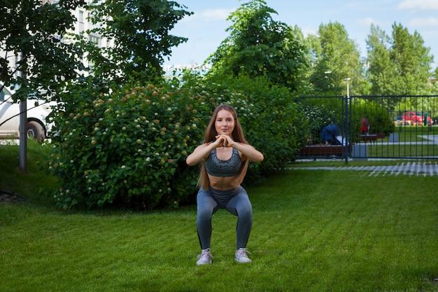 Uma desportista de mulher magra bonita fazendo agachamento em um gramado verde no parque em um dia de verão