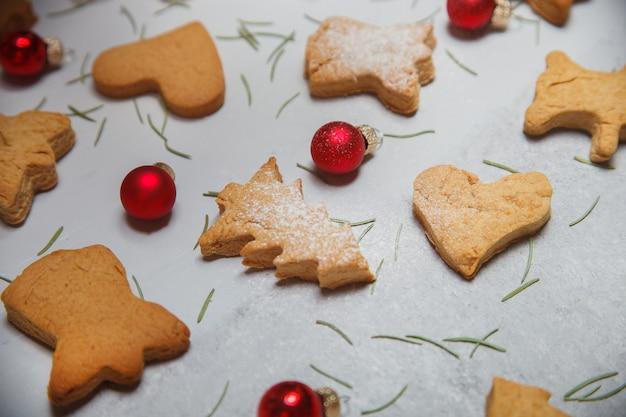 Uma dispersão de biscoitos de natal em uma superfície cinza. layout plano. vista do topo. conceito de natal e ano novo. cozinhando