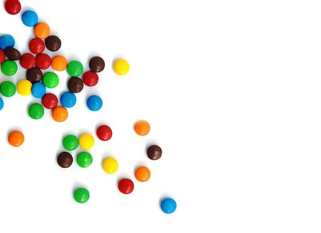 Uma dispersão de chocolates pequenos coloridos sobre um fundo branco.