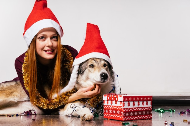 Uma doce garota ruiva com um boné vermelho e um enfeite dourado no pescoço está andando no chão com seu cachorro, esperando o ano novo 2018