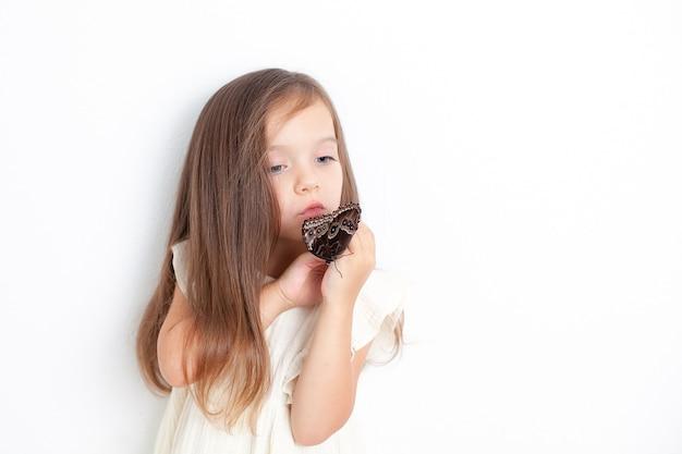 Uma doce menina segura uma borboleta morfo nas mãos e a examina. fundo branco, espaço para texto. o estudo da natureza. respeito. foto de alta qualidade