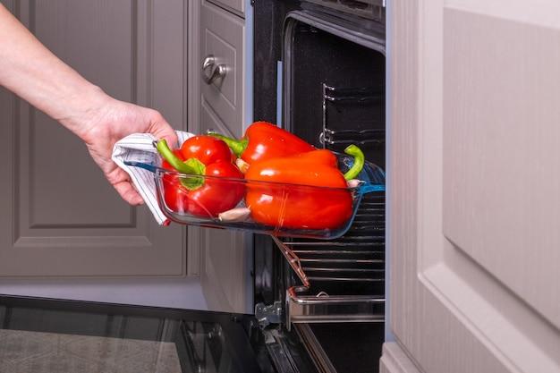 Uma dona de casa coloca uma bandeja de vidro à prova de fogo com pimentões vermelhos maduros para assar em um forno elétrico.