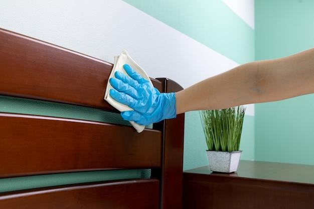 Uma dona de casa de camisa está limpando a casa, limpa a poeira da mesa com um pano de limpeza
