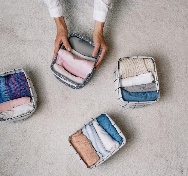 Uma dona de casa organizada coloca as coisas em um recipiente de lavanderia durante a limpeza geral com a ajuda de um moderno sistema de armazenamento. vista superior o conceito de uma organização bonita e confortável