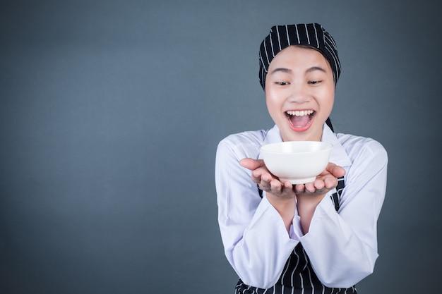 Uma dona de casa segurando um prato vazio com comida