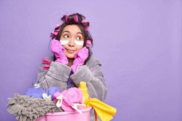 Uma dona de casa sonhadora e pensativa segura o queixo, perdida em pensamentos, usa rolos de cabelo e manchas de colágeno sob os olhos, posa perto da bacia de roupa suja com detergentes isolados sobre a parede roxa
