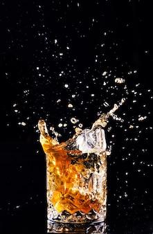 Uma dose de uísque com respingos na superfície preta, conhaque em um copo