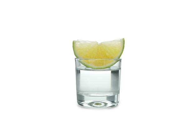 Uma dose de vodka e uma fatia de limão isolada na superfície branca