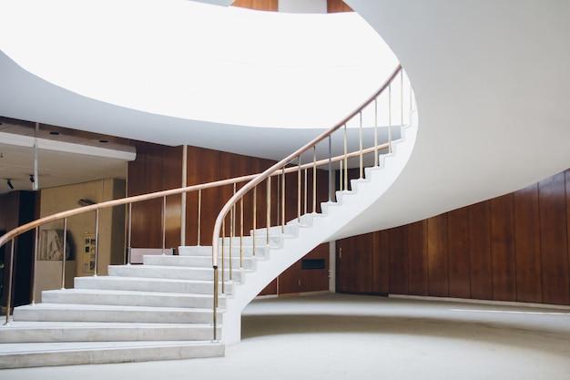 Uma elegante escada branca espirala para cima
