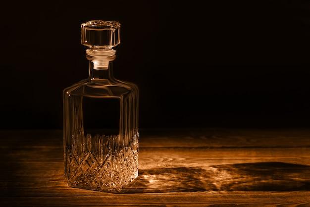 Uma elegante jarra vazia, sobre uma mesa de madeira texturizada. jarra em estilo escuro.