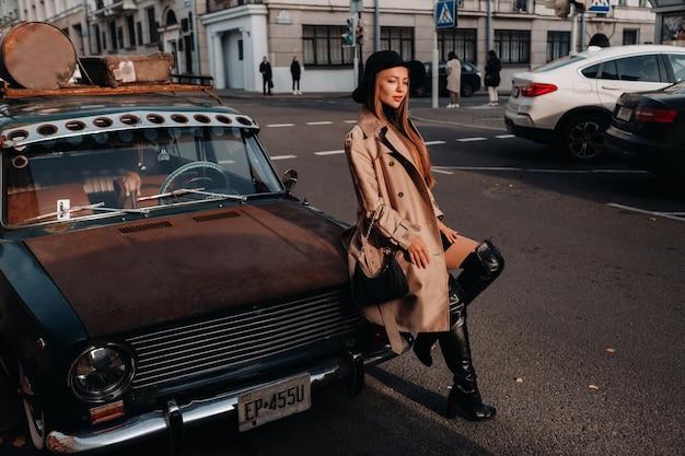 Uma elegante jovem com um casaco bege e chapéu preto em uma rua da cidade senta-se no capô de um carro ao pôr do sol. moda feminina de rua. roupas de outono. estilo urbano.
