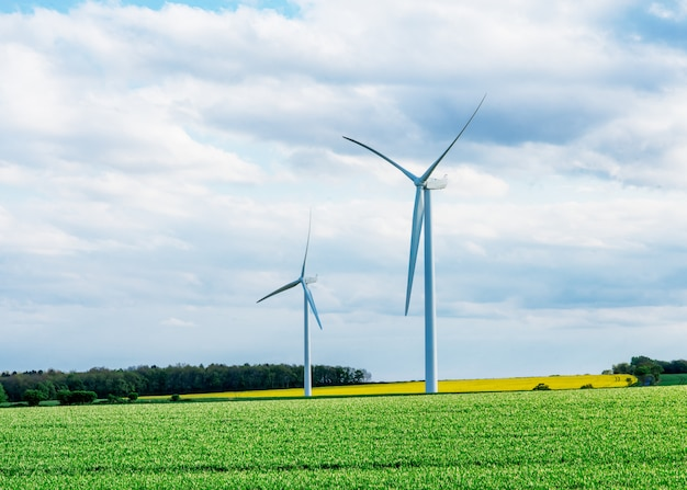 Uma eletricidade gerando moinhos de vento no campo amarelo e verde contra o céu azul nublado na inglaterra
