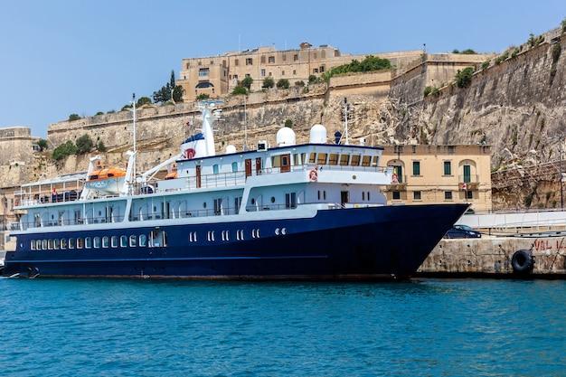 Uma embarcação de alta velocidade na cor branca para uso privado no fundo de outras embarcações.