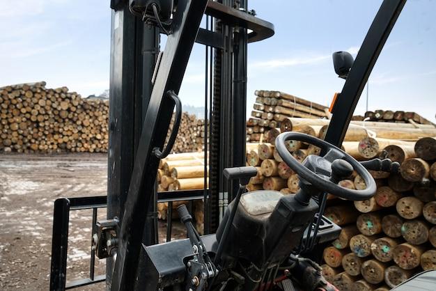 Uma empilhadeira está estacionada em uma fábrica de madeira