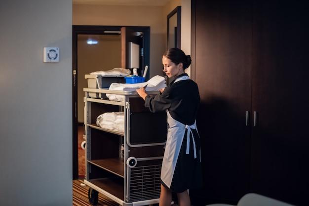 Uma empregada doméstica de uniforme entrando em uma sala com um carrinho