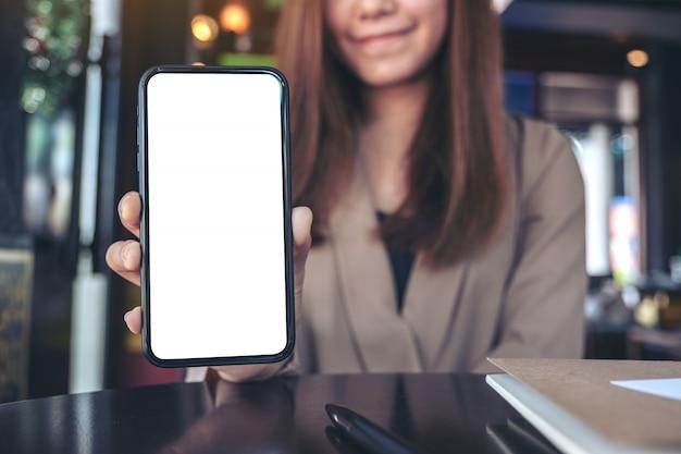 Uma empresária asiática segurando e mostrando um telefone celular preto com uma tela em branco em um café