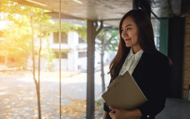 Uma empresária bem-sucedida asiática em pé no escritório