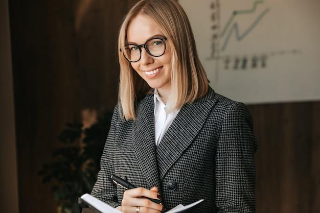 Uma empresária com um caderno nas mãos está parada e sorrindo no escritório, fazendo anotações e elaborando um novo plano de negócios para a empresa.